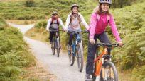 Parents et leur adolescente faisant du vélo à la campagne