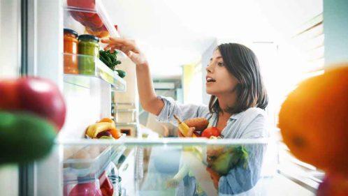 Femme cherchant des aliments dans son réfrigérateur