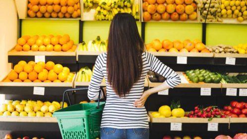 Jeune femme devant un rayon de fruits et légumes