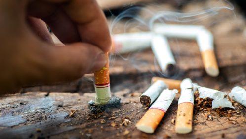 Personne en train d'écraser sa cigarette dans un cendrier déjà bien rempli.