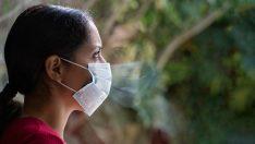 Photo d'une jeune femme portant un masque et s'inquiétant pour l'avenir de la planète