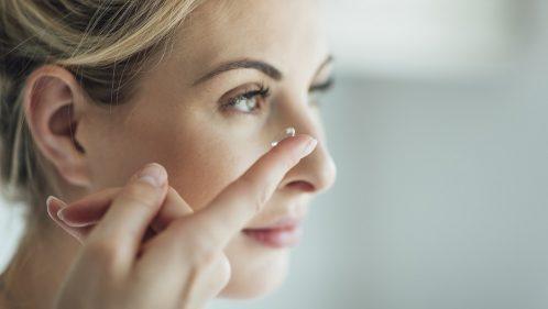 Une femme met sa lentille de contact